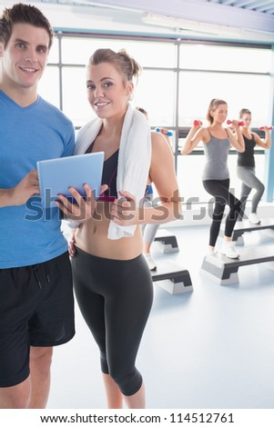 Woman and trainer looking at timetable in aerobics class in gym - stock photo
