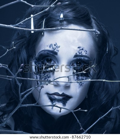 Woman and twigs. Romantic portrait of young lady with creative make-up.