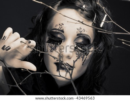 Woman and twigs. Romantic portrait of young lady with freative make-up. - stock photo
