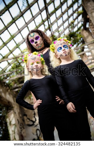 Woman and twin sisters with halloween makeup in abandoned house - stock photo