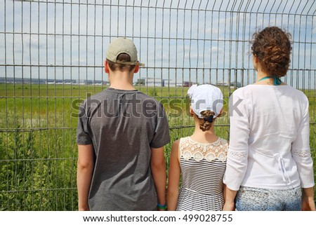 Woman and two children standing near fence of airport, back view