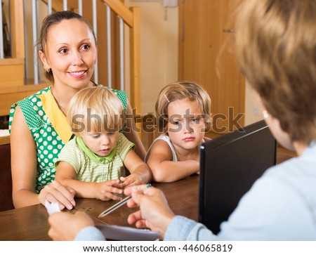 Woman and two daughters sitting in front of social worker - stock photo