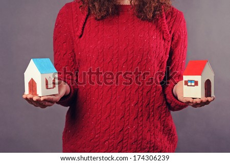 Woman and two Houses in hands on the gray background - stock photo