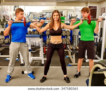 Woman and two men working his arms and chest at gym. She lifting barbell. - stock photo