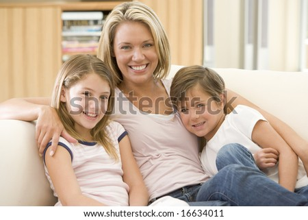 Woman and two young children in living room smiling - stock photo