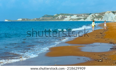 Woman and Xi Beach with red sand. Morning view (Greece, Kefalonia). Ionian Sea.