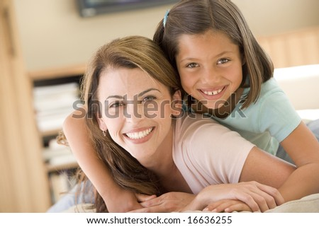 Woman and young girl in living room smiling - stock photo