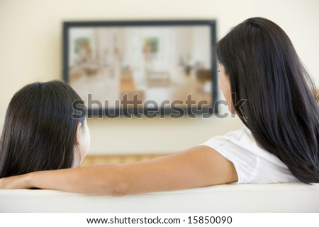 Woman and young girl in living room with flat screen television - stock photo