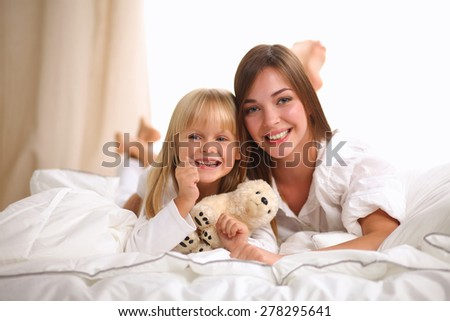 Woman and young girl lying in bed smiling . - stock photo
