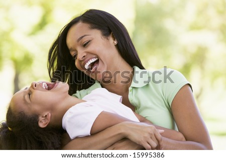 Woman and young girl outdoors embracing and laughing - stock photo