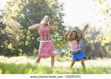 Woman and young girl outdoors using hula hoops and smiling - stock photo
