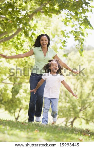 Woman and young girl running outdoors smiling - stock photo