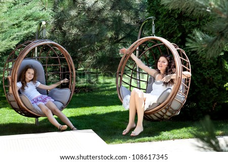 Woman and young girl sitting on patio - stock photo