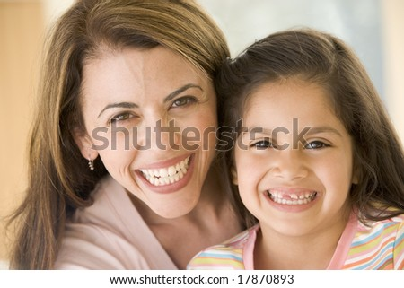 Woman and young girl smiling - stock photo