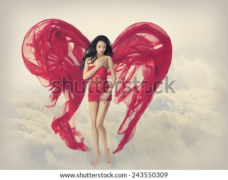Woman  Angel with Wings In Heart Shape. Fashion Red Dress, Fabric Cloth Waving On Wind, Flying Girl In Fluttering Gown. Artistic Fantasy Sky Background.  - stock photo