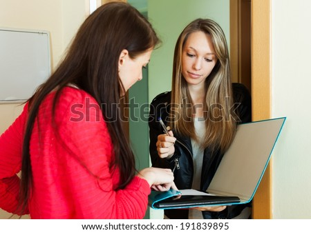 Woman answer questions of smiling girl with papers at door at home