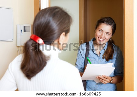 woman answers the questions in the door at home - stock photo