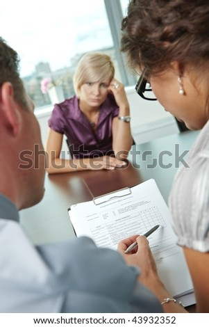 Woman applicant having failed job interview. Over the shoulder view. Focus placed on sheet in front all results are bad. - stock photo