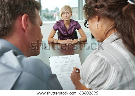 Woman applicant worrying during job interview. Over the shoulder view. Focus placed on sheet in front all results are bad.? - stock photo