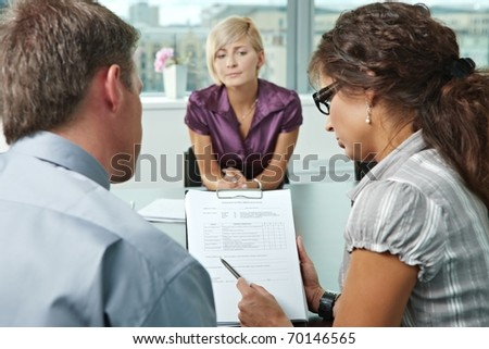 Woman applicant worrying during job interview. Over the shoulder view. Focus placed on sheet in front results are good.? - stock photo