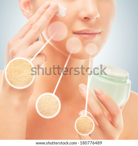 Woman applies moisturizer cream on face, concept of skincare, in circles dry skin before cream - stock photo