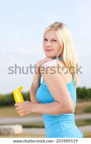 Woman applies sun lotion - stock photo