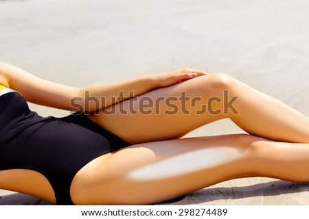 Woman apply sun protection cream on   her smooth tanned legs - stock photo