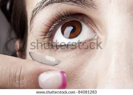Woman applying a Contact Lens on her eye - stock photo