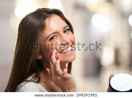 Woman applying a moisturizer on her face - stock photo