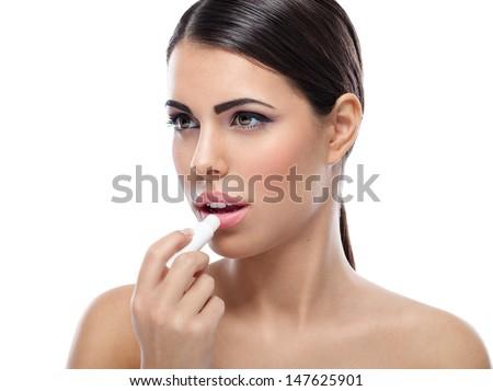 woman applying balsam on lips - stock photo