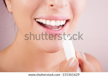 woman applying balsam on lips