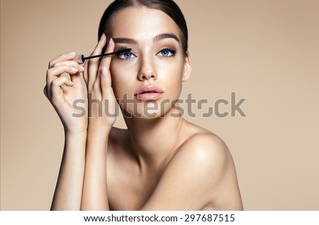 Woman applying black mascara on eyelashes with makeup brush / photos of appealing brunette girl on beige background - stock photo