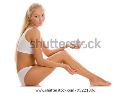 Woman applying body cream - stock photo