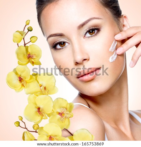 Woman applying cosmetic cream on the face - stock photo