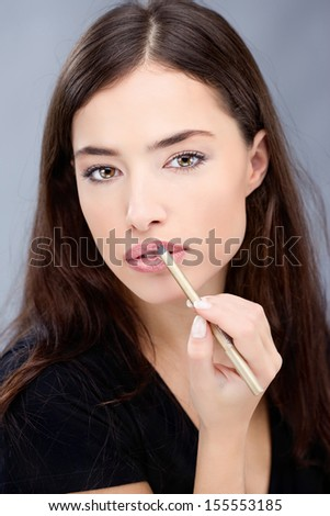 Woman applying cosmetic pencil on lips - stock photo