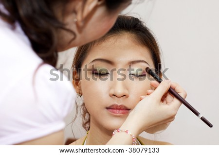Woman applying cosmetic with applicator. Make-up treatment. - stock photo