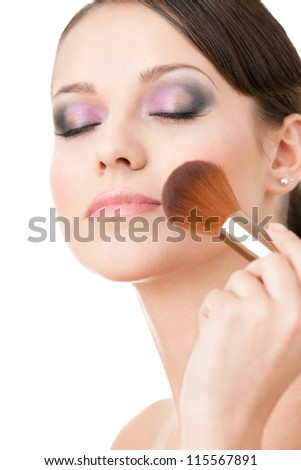 Woman applying cosmetics to her face with eyes shut with the help of cosmetic brush, isolated on white - stock photo