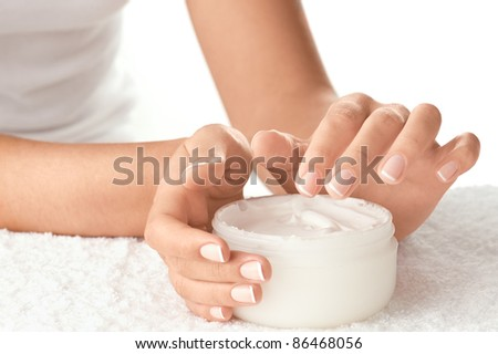 Woman applying cream isolated on white background - stock photo