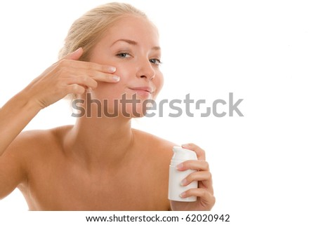 Woman applying cream on cheek - stock photo