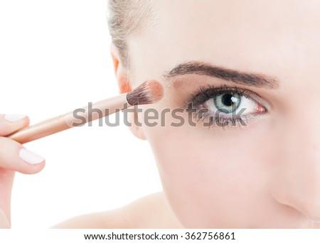 Woman applying daytime make-up using eye brush - stock photo