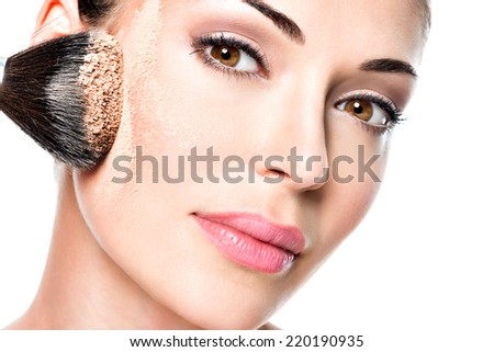 woman  applying dry cosmetic tonal foundation  on the face using makeup brush.  - stock photo