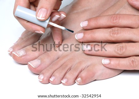 Woman applying enamel on toes and finger nails - stock photo