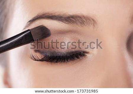 Woman applying eyeshadow - stock photo