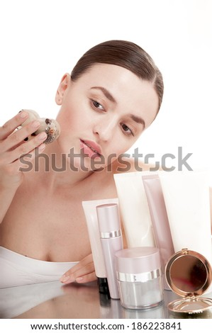 Woman applying  ice cube treatment on face - isolated on white background. - stock photo