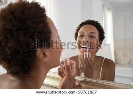 Woman applying lip gloss in mirror, at home