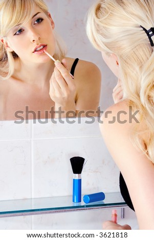 woman applying lipstic in front of mirror in bathroom - stock photo