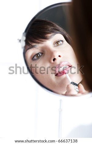 Woman applying lipstick in the mirror