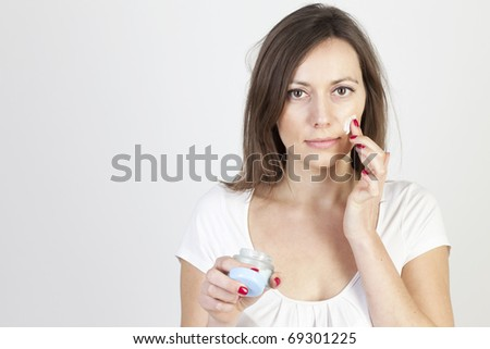 Woman applying lotion on her face