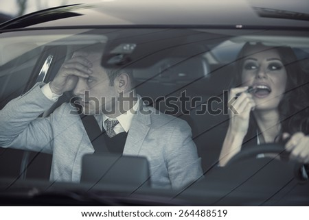 Woman applying make-up while driving - stock photo