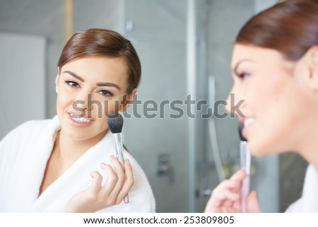 Woman applying make up with cosmetic brush - stock photo